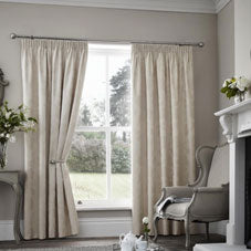 Cream pencil pleat curtains at a window