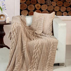 A beige woven throw draped over a cream armchair