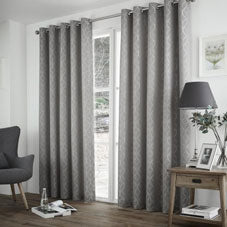 Grey eyelet curtains at a living room window
