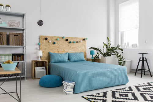 Modern Scandinavian style bedroom with duck egg blue double bed with chipboard headboard covered in fairy lights