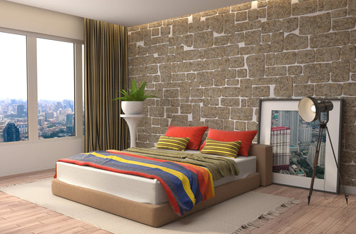A low double bed with blue, yellow, red and orange striped bedding
