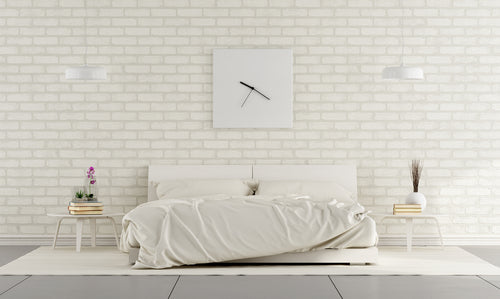 Brick wall painted white with a low white double bed and white square wall clock