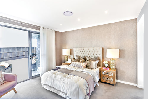 Cream and beige bedroom with double bed, two bedside tables and lots of light coming through the window and patio door
