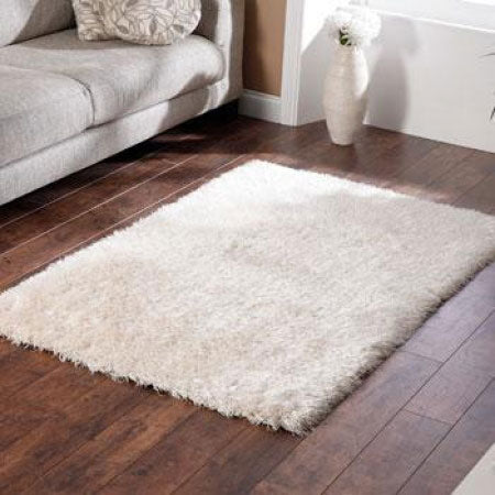 White fluffy rug on dark wooden flooring