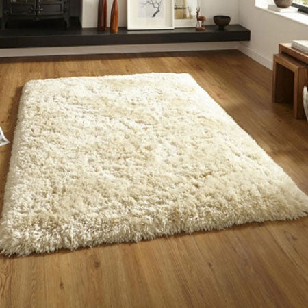 Cream shaggy rug on light wooden flooring
