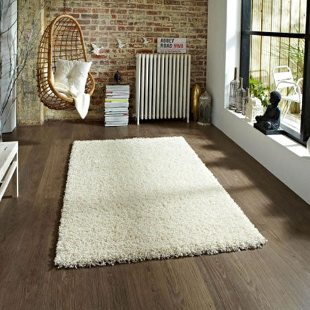 Cream shaggy rug on dark laminate flooring