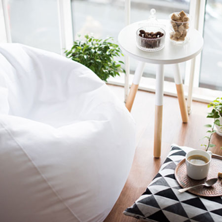 White round side table with tripod legs, next to a white bean bag