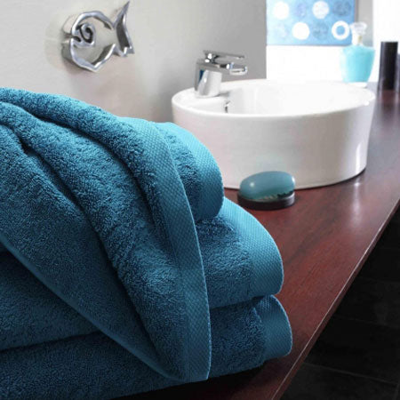 Dark blue towels on a dark wooden counter in a bathroom