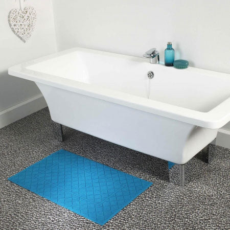 Bright blue bathroom mat in front of a white bath