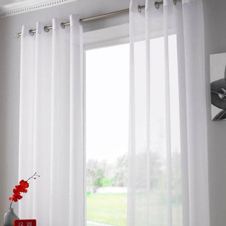 White eyelet voiles at a window