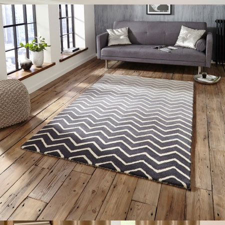 Black and white zig-zag striped rug on wooden flooring