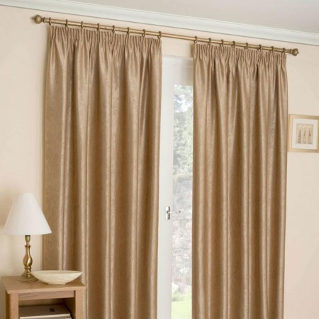 Beige shimmering pencil pleat curtains at a window
