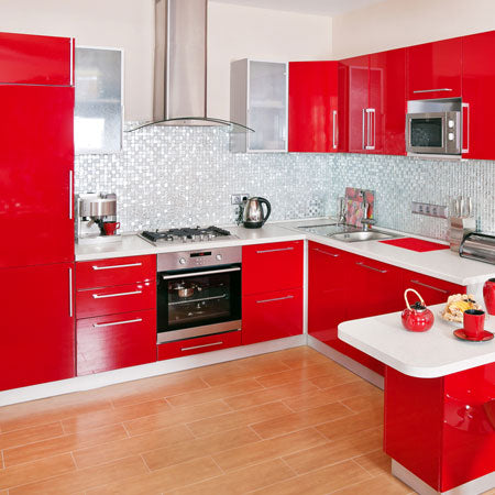 Grey wall tiles and laminate flooring in a kitchen with bright red kitchen units