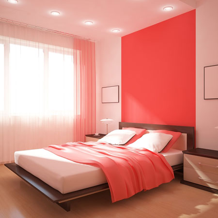 Birght bedroom with sunlight through voile curtains and white and coral colour scheme