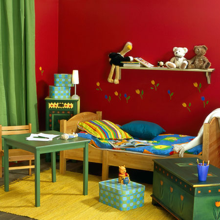Dark red and dark green childrens room with green table and wooden bed with bright bedding