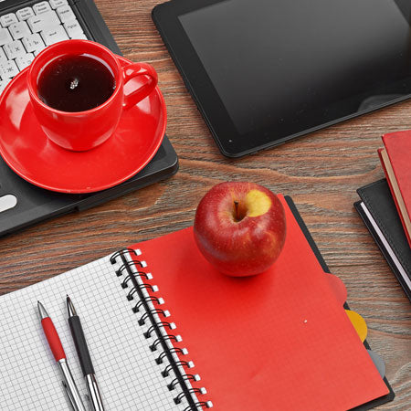 a close up of an office desk with Filofax, red coffee cup, black laptop and tablet