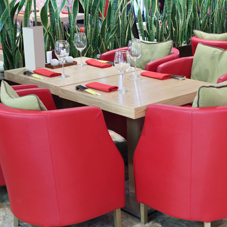 Red round leather armchairs around a table in a restaurant