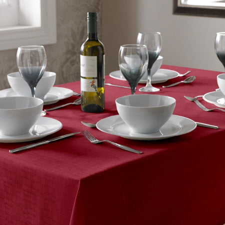 Dark red table cloth on a table with white soup bowls and wine glasses