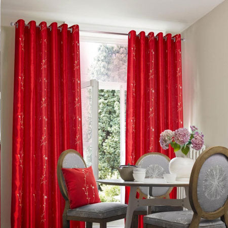 Bright red eyelet curtains at patio garden doors in a dining room