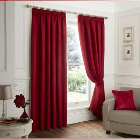 Dark red pencil pleat curtains at a window in a cream living room