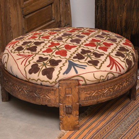 A wooden footstool with a fabric top that has a brown and red geometric floral pattern