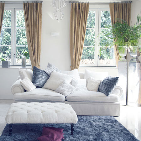 Cream sofa with cream and blue cushions, dark blue rug and beige pencil pleat curtains in the background