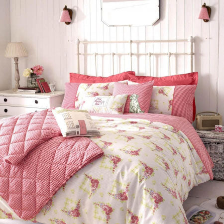 Cream and pink bedding on a white metal bed frame