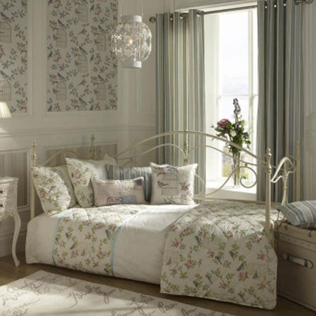 White metal day bed frame with cream and floral bedding