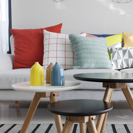 Red, white and duck egg blue cushions on a grey sofa