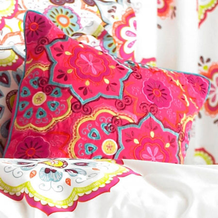 Bright pink cushion with teal and yellow floral pattern