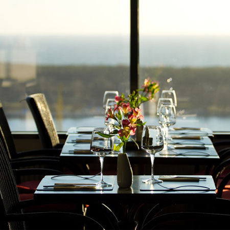 A restaurant table at a window, overlooking the sea
