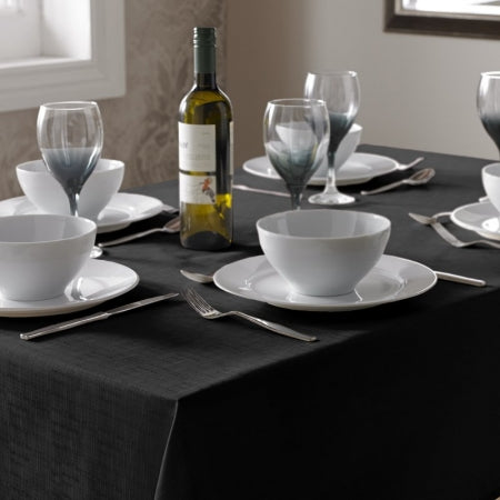 A black table cloth on a table, with white bowls, plates, wine and glasses on top