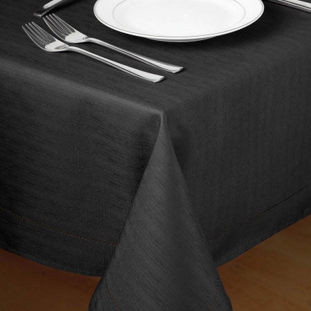 Black table cloth on a table with a white plate and two forks on top