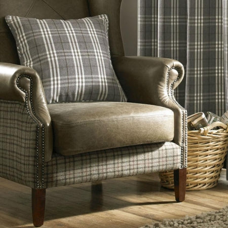A checked grey and white cushion on a comfy beige armchair