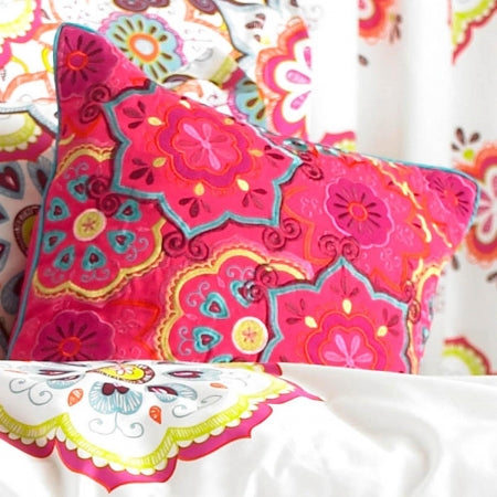 A dark pink cushion with teal and mustard modern floral design