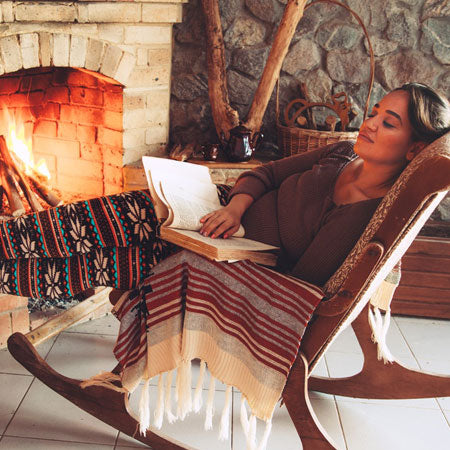 A woman relaxing on a rocking chair by a wooden log fire, reading a book