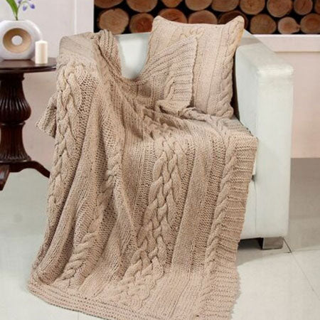 A beige woven throw draped over a white armchair