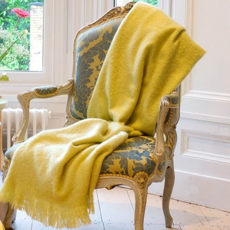 A yellow throw draped over a wooden upholstered dining chair