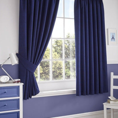 Dark blue curtains in a white and blue bedroom