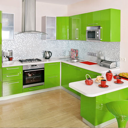 Laminate flooring and grey wall tiles in a kitchen with bright green kitchen units