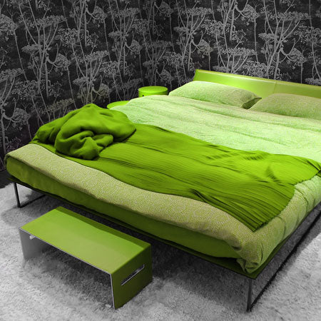 Bright green bedding on metal frame double bed in a room with black and grey woodland wallpaper