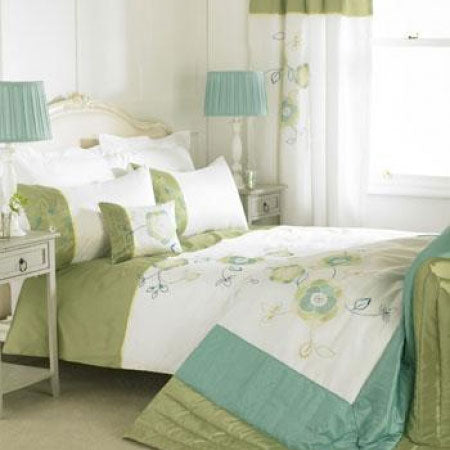 White and green floral bedding on a cream wooden double bed