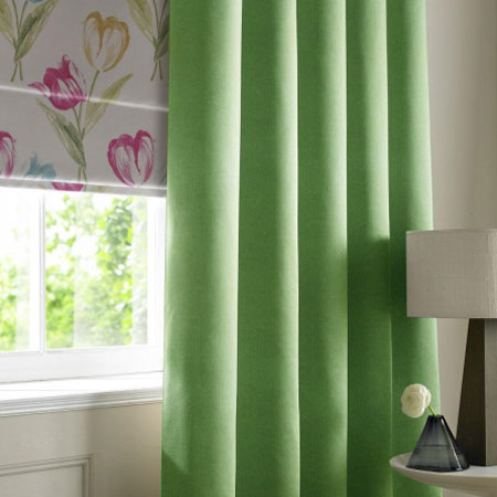 Vibrant green curtains at a window, that also has a cream roman blind with bright flower design
