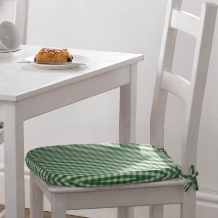 A white dining table and chair, with a green plaid seat pad