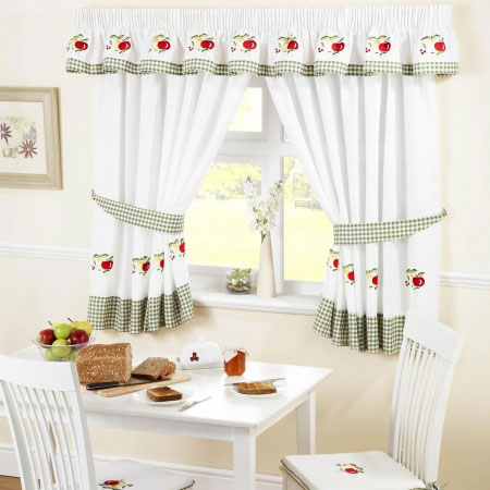 White kitchen curtains with a green plaid trim and red apple design