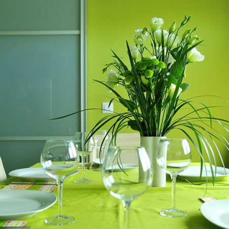 A very green dining room with green walls and green dining table, plus flowers in a vase on the table