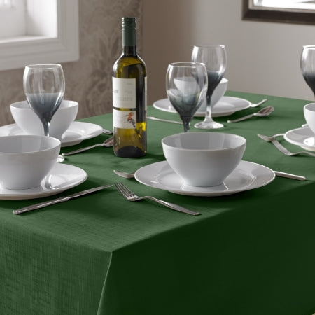A dark green table cloth on a table, with white soup bowls and bottle of wine on the table