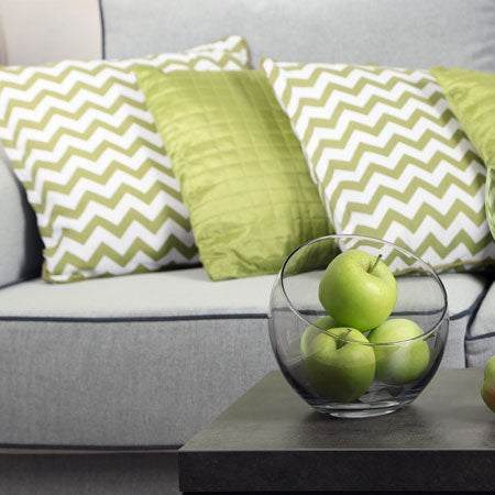 Green cushions on a grey sofa, one cushion is white and green with a zigzag striped pattern and the other is solid green