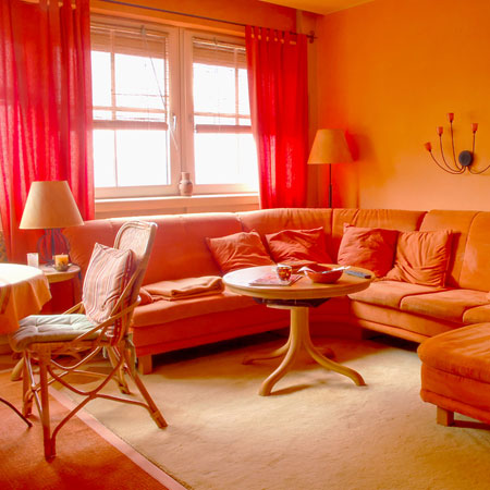 A living room with all furniture, cushions and walls orange