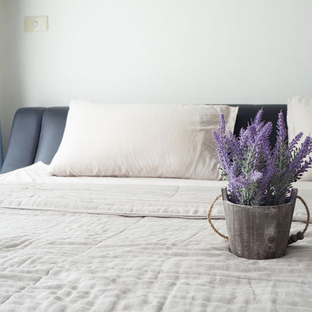 White bedding with a bucket of lavender on the foot of the bed